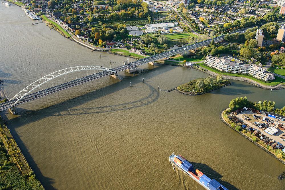 Nederland, Zuid-Holland, Dordrecht, 23-10-2013;  Papendrechtse brug (N4) over de Beneden-Merwede naar Papendrecht. Containerschip vaart over de rivier. Middenboven rioolwaterzuiveringsinstallatie.<br /> Road bridge on the river Beneden-Merwede.<br /> Container ship sails along.<br /> luchtfoto (toeslag op standaard tarieven);<br /> aerial photo (additional fee required);<br /> copyright foto/photo Siebe Swart.