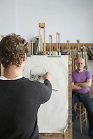 Artist drawing charcoal portrait of model in studio back view