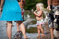 JEROME A. POLLOS/Press..Lilly Sherar, 2, enjoys a popsicle on the shoreline of the Spokane River as her family feeds birds Monday.