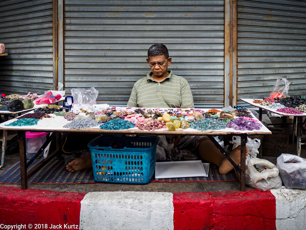 22 DECEMBER 2018 - CHANTABURI, THAILAND: A Thai man selling gems and precious stones in the Chantaburi gem market. The gem market in Chantaburi, a provincial town in eastern Thailand, is open on weekends. Chantaburi used to be an active gem mining area in Thailand, but the mines are played out now. Now buyers and sellers come from around the world to Chantaburi for the weekend market. Many of the stones come from Myanmar, others come from mines in Afghanistan and Africa.     PHOTO BY JACK KURTZ