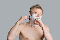 Young shirtless man covering mouth while shaving over colored background