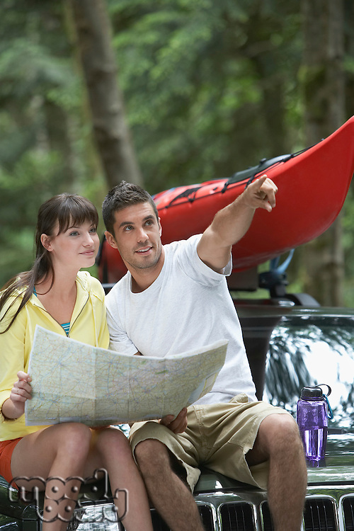 Couple sitting on car looking at map man pointing