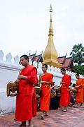 Monks and tourists particate in sai bat (morning alms giving), Luang Prabang, Laos.