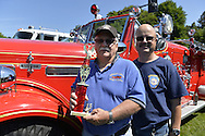 Old Westbury, New York, United States. 7th June 2015. Ex-Chief NIEL HICKS, holding trophy the Manhasset-Lakeville Fire Dept. Truck won in fire truck category, and fire fighter ALEX SEQUEIRA are posing by the fire truck at the 50th Annual Spring Meet Car Show sponsored by Greater New York Region Antique Automobile Club of America. Over 1,000 antique, classic, and custom cars participated at the popular Long Island vintage car show held at historic Old Westbury Gardens.