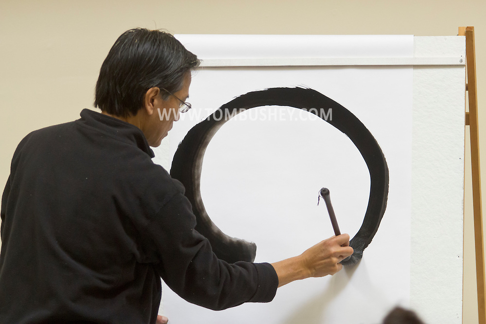 Middletown, N.Y. - Artist Ron Gee demonstrates the techniques of brush work that both calligraphy and painting share during a Master Class at SUNY Orange on Nov. 14, 2013.
