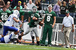 17 September 2011: A defender get an ankle hold on Cameron Blossom during an NCAA Division 3 football game between the Aurora Spartans and the Illinois Wesleyan Titans on Wilder Field inside Tucci Stadium in.Bloomington Illinois.