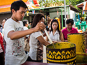 11 JULY 2014 - BANGKOK, THAILAND:   Thai Buddhists make candles for Asalha Puja Day. Asalha Puja is the day the Lord Buddha preached his first sermon to followers after attaining enlightenment. The day is usually celebrated by merit making and listening to a monks' sermons. It is also day before the start of the Rains Retreat, the three month period when monks stay in their temple for intense mediation and spiritual renewal. Making candles is a traditional way of making merit before the Rains Retreat because candles were essential in former times for both ceremonies and studying scriptures during night time. The large candles that are made and given to the temple to create illumination in the belief that such a gift will likewise illuminate the mind.   PHOTO BY JACK KURTZ