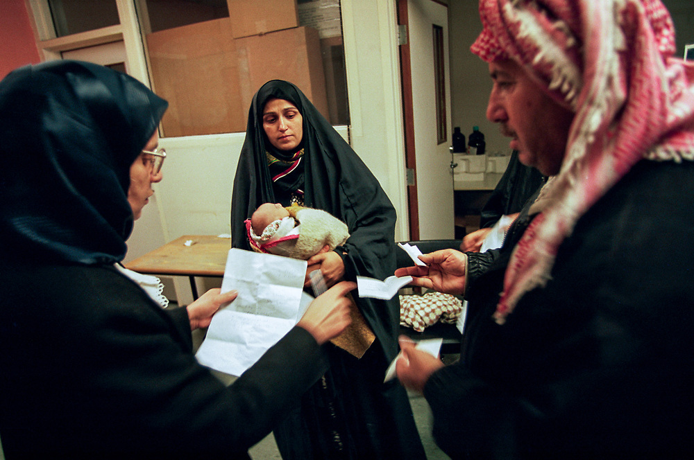 Parents seeking treatment for their child born congenitally deformed from Dr. Selma al-Taha (left), a genetic specialist, at the Baghdad Medical College hospital. Cases of congenital anomolies have risen sharply in Iraq since the Gulf War.<br />