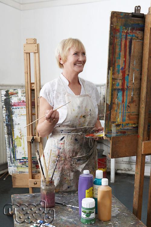 Mature female artist painting at easel in art studiocanvas in studio