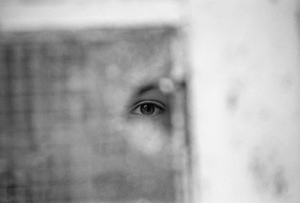 A boy is looking through a hole in a broken window at the Varazdin refugee camp in Croatia in the winter of 1992.