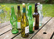 Empty glass bottles standing on a table outdoors in sunshine, UK