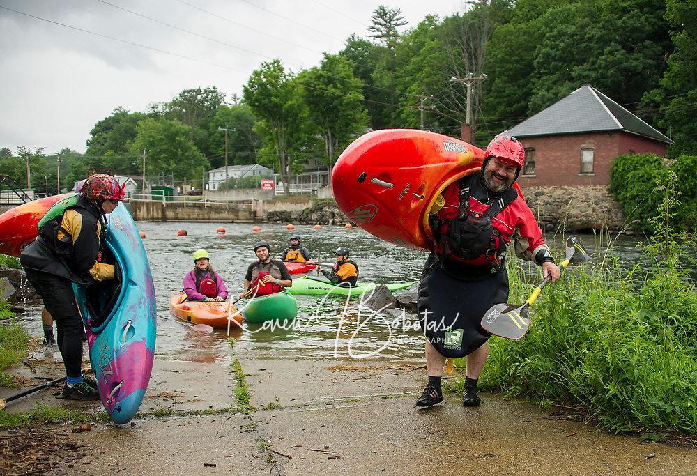 "Jeff Magee of Enfield, CT hauls out his kayak ready for another run down the Winni River during Mill City Park's ""Winni River Days"" whitewater festival in Franklin on Saturday.  (Karen Bobotas/for the Laconia Daily Sun)"