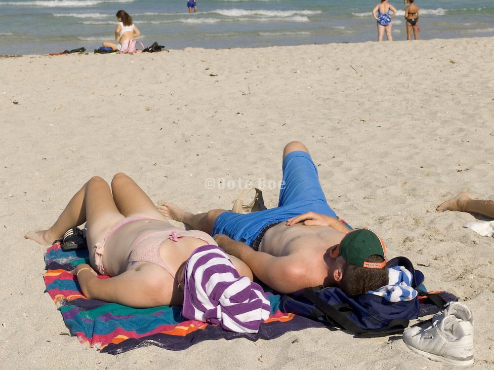 young couple sunbathing on beach Miami USA