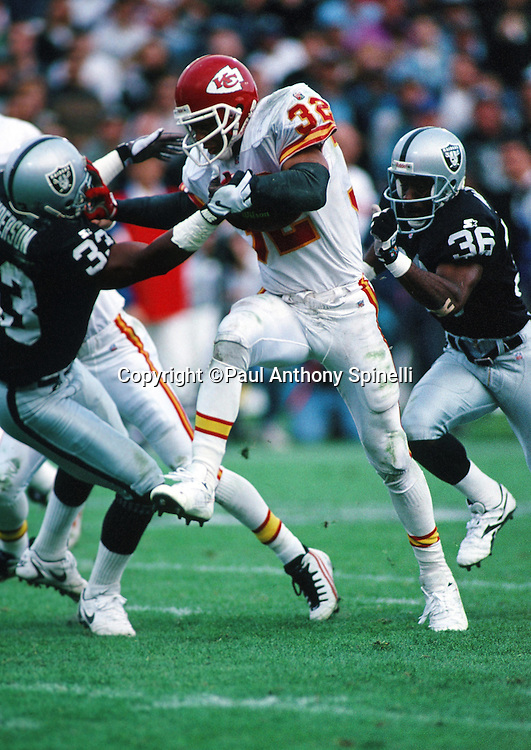 Kansas City Chiefs running back Marcus Allen (32) high steps as he sets the record for all-time rushing (10,000 yards) and receiving (5,000 yards) as he runs the ball during the NFL football game against the Oakland Raiders on Dec. 3, 1995 in Oakland, Calif. The Chiefs won the game 29-23. (©Paul Anthony Spinelli)