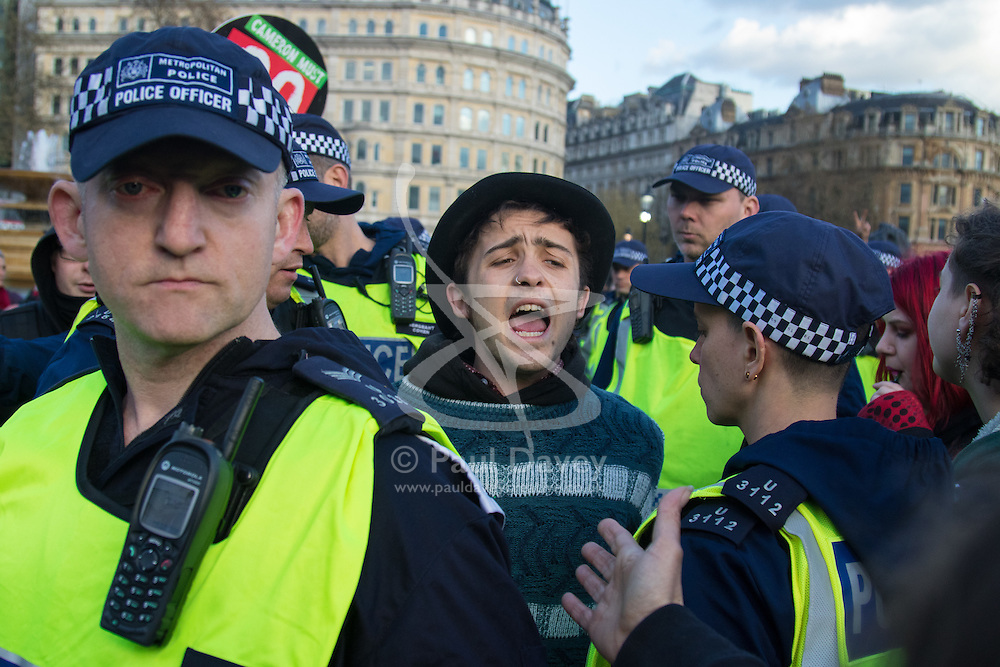 """London, April 16th 2016. A young man shouts as he is detained by police officers in Trafalgar Square, after thousands of people supported by trade unions and other rights organisations demonstrate against the policies of the Tory government, including austerity and perceived favouring of """"the rich"""" over """"the poor""""."""