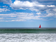 A red sailboat on the Maine coast with blue sky, white clouds, green water and white surf