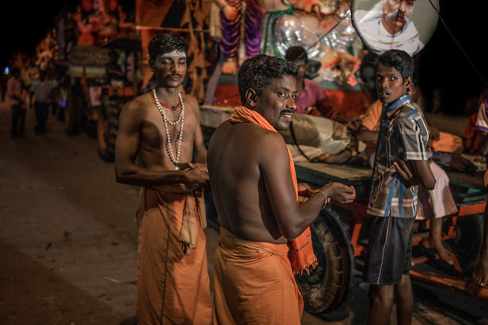 Local men dressed in pilgrim's garb standing in front of a long line of Lord Ganesha statues on the back of trucks and trailers at the Ganesh Chaturthi Festival.  Pondicherry, India