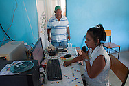 """Minerva Gil (on microphone) speaks in the community radio """"Superactivo"""" in Huamuxtitlán when Miguel Buitrago (back) finishes his program """"Rescatemos lo Nuestro"""".  Huamuxtitlán communities, conformed more from mestizo people, started their own justice group in 2011, named Citizen Council and inspired in the Community Police, after suffering kidnappings in the town in complicity with local authorities, including ministerial police and mayoress. / Minerva Gil (al micrófono) habla en la radio comunitaria """"Superactivo"""" en Huamuxtitlán, al finalizar Miguel Buitrago su programa """"Rescatemos lo Nuestro"""". Las comunidades de  Huamuxtitlán comenzaron su propio grupo de justicia en 2011, llamado Consejo Ciudadano e inspirado en la Policía Comunitaria, despuÈs de sufrir secuestros en complicidad con autoridades locales que incluÌan a la policÌa ministerial y la alcaldesa. (Photo: Prometeo Lucero)"""