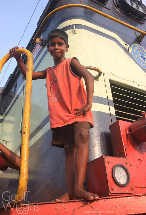 Indian boy playing on railway locomotive at Puducherry station in the Indian union territory of Puducherry