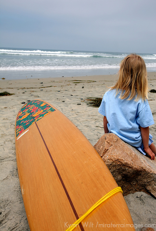 Woman's surfboard and unidentifiable young girl watching the waves.