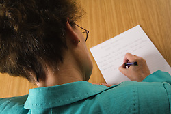 Older woman writing at a table,