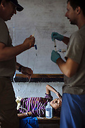 Volunteers Dr. Rick Bowen (left) and nurse Daniel Danilczyk place an IV line in a young patient as they treat her for infected wounds on her leg and foot at Himalayan Family Healthcare Project medical camp in Thonche, Nepal.
