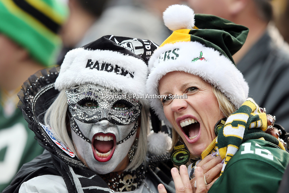 An Oakland Raiders fan wearing a mask and a painted face with team colored apparel yells out while posing for a photo with a Green Bay Packers fan, both of whom are wearing Christmas Santa Claus hats during the Oakland Raiders 2015 week 15 regular season NFL football game against the Green Bay Packers on Sunday, Dec. 20, 2015 in Oakland, Calif. The Packers won the game 30-20. (©Paul Anthony Spinelli)