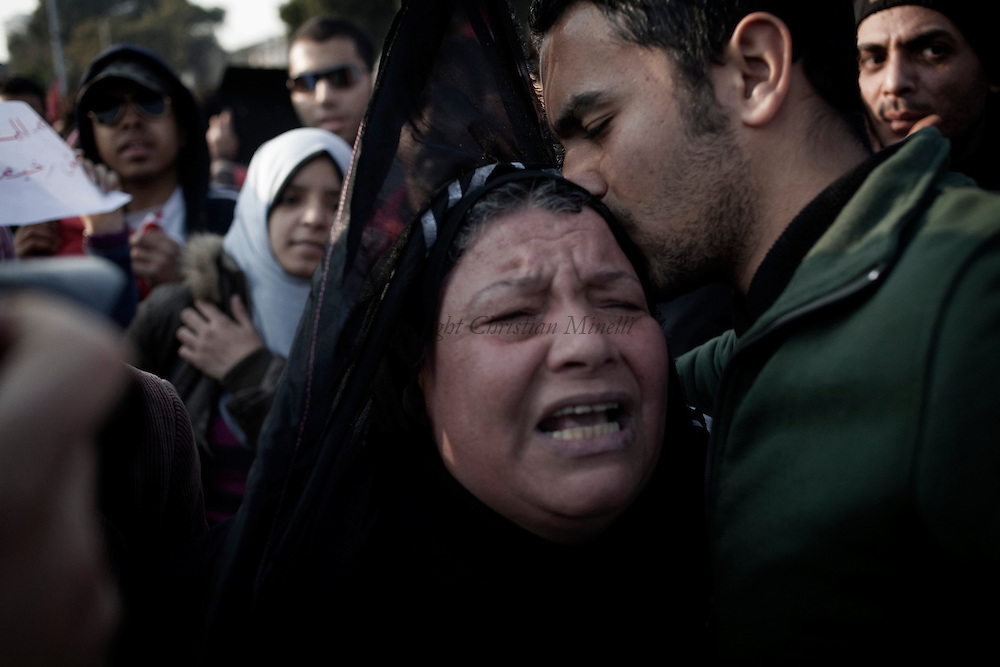 EGYPT, Cairo: An Egyptian comforts a woman  during a march the day after deadly clashes at a soccer stadium in Port Said, Egypt, Thursday, Feb. 2, 2012.