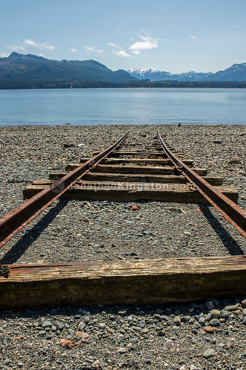 Rusted train tracks on a pebble beach in British Columbia, Canada.