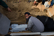 Palestinians bury a 12 year old boy killed during an Israeli airstrike January 16, 2009 in Rafah Gaza. The Israeli Defense Forces claim their sustained campaign has significantly degraded smuggling tunnels along  the corridor and the damaged the ability of HAMAS to smuggle weapons and cash into the Strip, but it has also killed civilians unlucky to have been still in the vicinity of targeted neighborhoods.