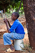 A young boy reads a book in the peace and quite of the garden at the AFCIC centre in Thika, Kenya. AFCIC - Action for children in conflict, help children who have been affected by various forms conflict or crisis.