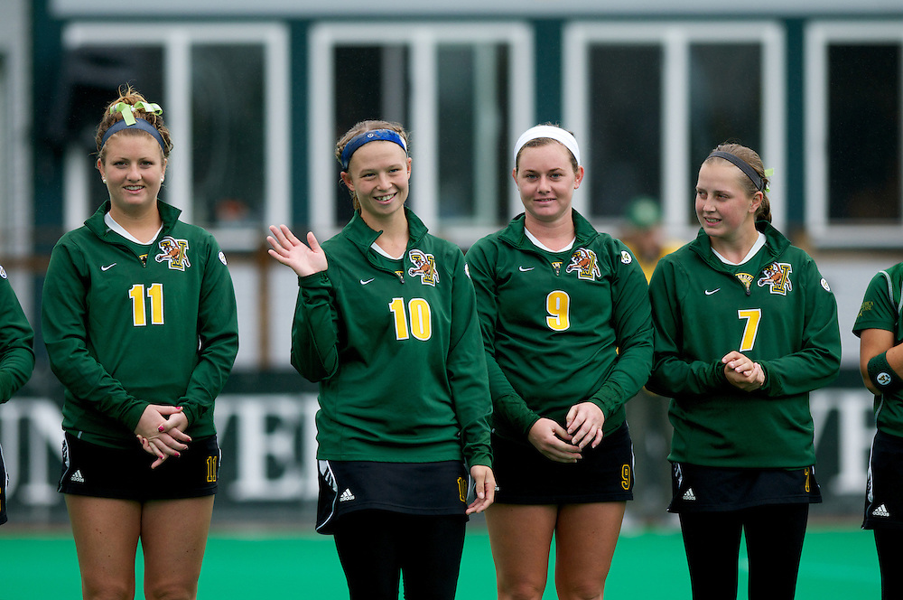Catamounts defenseman Jackie Bendick (10) waves to the crowd as Catamounts midfielder Callie Bellimer (11), Catamounts forward Colleen Slaughter (9) and Catamounts midfielder Kalla Gervais (7) look on during player introductions before the start of the women's field hockey game between the Maine Black Bears and the Vermont Catamounts at Moulton/Winder Field on Saturday afternoon September 29, 2012 in Burlington, Vermont.