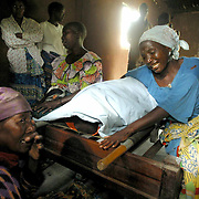 May 31, 2003 - Family members weep over the body of Samuel Unega, 70, who died earlier in the day. Unega died from machete wounds to the head when his village was attacked by Lendu rebels two weeks before during fighting in the town of Bunia, Congo. Photo by Evelyn Hockstein