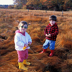"Young friends play on a New Hampshire salt marsh. Tidal marsh.  ""Massacre Marsh.""Rye, NH"
