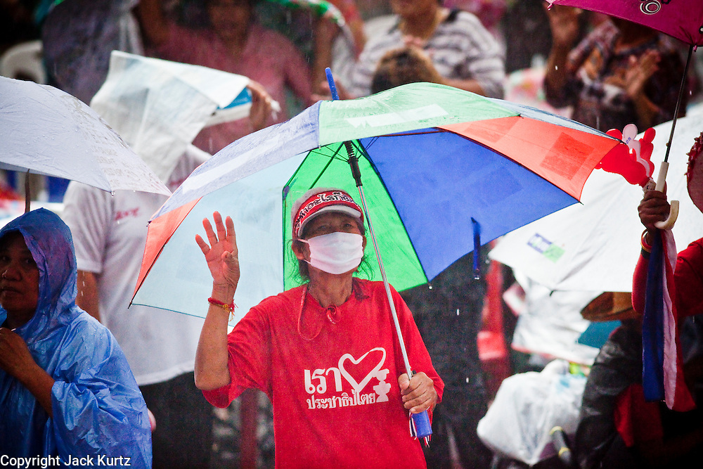 04 MAY 2010 - BANGKOK, THAILAND:  Red Shirt protesters listen to speakers and party in the rain in front of their main stage at Ratchaprasong intersection in Bangkok Tuesday. Red Shirt protesters continued their actions in Bangkok Tuesday despite heavy thunderstorms that brought rain to the city. The Red Shirts have conditionally accepted the offer of Thai Prime Minister Abhisit Vejjajiva to dissolve parliament, investigate alleged human rights violations following the violence of April 10 and call for new elections in November of this year, 18 months earlier than they are currently scheduled, but they want more negotiation before they finalize any agreements. They said their protests would continue until a final agreement is reached. The Red Shirts, started their protest on March 13. They continue to call for Thai Prime Minister Abhisit Vejjajiva to step down and dissolve parliament immediately and demand the return of ousted Prime Minister Thaksin Shinawatra.     PHOTO BY JACK KURTZ