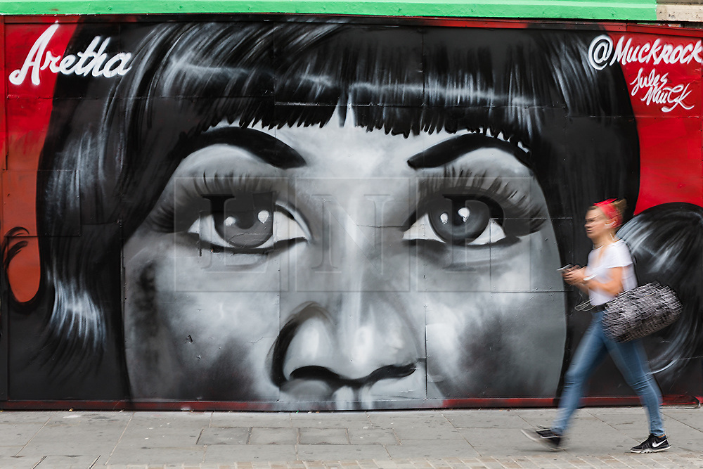 © Licensed to London News Pictures. 19/08/2018. London, UK.  A woman walks past new street art in Shoreditch, east London, paying tribute to the singer, Aretha Franklin who has died following a battle with pancreatic cancer.  The mural has been created by artist, Jules Muck in collaboration with Global Street Art. Photo credit: Vickie Flores/LNP