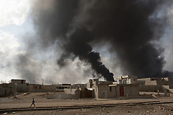 Licensed to London News Pictures. 02/11/2016. Qayyarah, Iraq. A child walks along disused railway tracks as thick smoke rises from boring oil wells, set alight by retreating Islamic State militants, in the town of Qayyarah, Iraq.<br /> <br /> Two months after being liberated from the Islamic State, the Iraqi town of Qayyarah, located around 30km south of Mosul, is still dealing with the environmental repercussions of their ISIS occupation. The town's estimated 15,000 inhabitants constantly live under, and in, heavy clouds of smoke which often envelope the settlement. The clouds emanate from burning oil wells in a nearby oil field that were set alight by retreating ISIS extremists after a two year occupation. The proximity of the fires, often right next to homes within the town, covers many buildings and residents with thick soot and will lead to long term health and environmental implications. Photo credit: Matt Cetti-Roberts/LNP