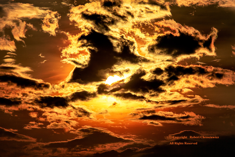Silhouette Vs. Gold: A dramatic, golden sunrise has the clouds turn black in silhouette, with the sun fighting to be exposed, over Senaru Lombok Indonesia.