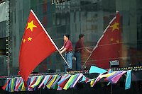 HONG KONG- JULY 1: A man puts out a large Chinese flag on a building in Wanchai prior to the handover celebration on June 30, 1997 in Hong Kong, China. On July 1, 1997 Hong Kong was handed over to China from the United Kingdom after being a colony for 150 years. (Photo by David Paul Morris) ..
