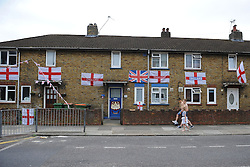 © Licensed to London News Pictures. 14/06/2014. West Ham, UK. A group of children walk past a terrace of houses in West Ham that are draped in England flags. Photo credit: LNP