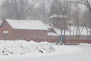 A tractor grooms the training surface at Goshen Historic Track in Goshen, New York, during a snowstorm.