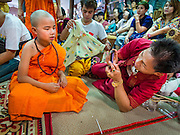 "06 APRIL 2015 - CHIANG MAI, CHIANG MAI, THAILAND: A boy just ordained as a Buddhist novice has his picture taken by a family member on the last day of the three day long Poi Song Long Festival in Chiang Mai. The Poi Sang Long Festival (also called Poy Sang Long) is an ordination ceremony for Tai (also and commonly called Shan, though they prefer Tai) boys in the Shan State of Myanmar (Burma) and in Shan communities in western Thailand. Most Tai boys go into the monastery as novice monks at some point between the ages of seven and fourteen. This year seven boys were ordained at the Poi Sang Long ceremony at Wat Pa Pao in Chiang Mai. Poy Song Long is Tai (Shan) for ""Festival of the Jewel (or Crystal) Sons.   PHOTO BY JACK KURTZ"