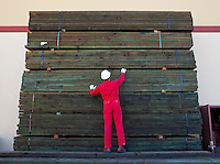 Hispanic worker inspecting timber wooden planks