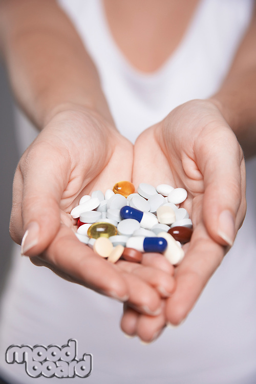 Woman holding pills in hands close-up on hands