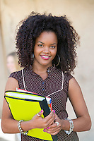 Student Holding Notebook and Textbooks