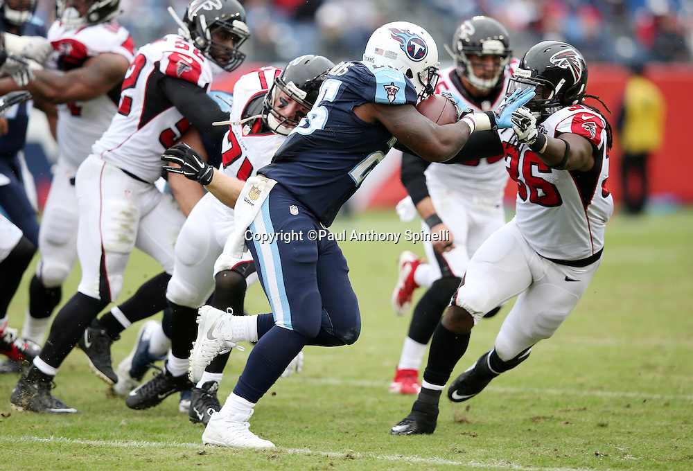Tennessee Titans running back Antonio Andrews (26) straight arms Atlanta Falcons strong safety Kemal Ishmael (36) as he runs the ball during the 2015 week 7 regular season NFL football game against the Atlanta Falcons on Sunday, Oct. 25, 2015 in Nashville, Tenn. The Falcons won the game 10-7. (©Paul Anthony Spinelli)