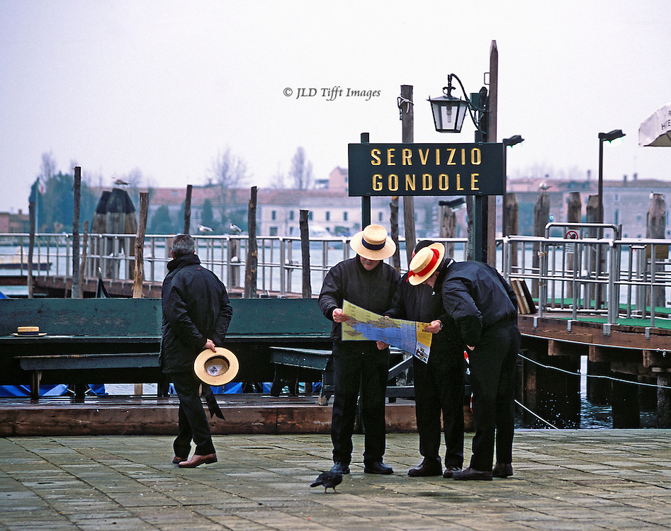 """Three gondolieri consult a map on the Riva del Schiavoni, Venice.  Two wear straw boaters, the third bare-headed.  A fourth walks away from them, holding his straw boater behind him.  Sign above their heads: """"Servicio Gondole."""".."""