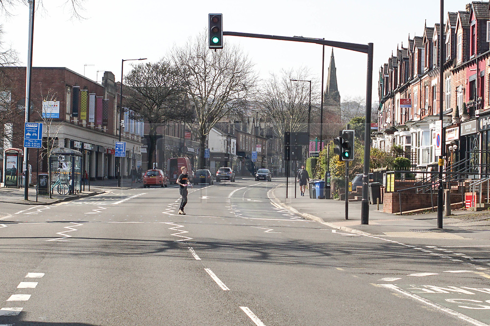 © Licensed to London News Pictures. 24/03/2020. Sheffield , UK. A man jogs as he crosses a street  on Ecclesall Road in Sheffield  , after the British government imposed a nationwide lockdown to contain the spread of the coronavirus disease. British Prime Minister Boris Johnson has announced ban on all non-essential movement outdoors or may be fined  in order to control the spread of the coronavirus outbreak. People only allowed to go out to buy food,  to buy medicine ,go to work and to do one form of exercise per day.  Photo credit: Ioannis Alexopoulos / LNP