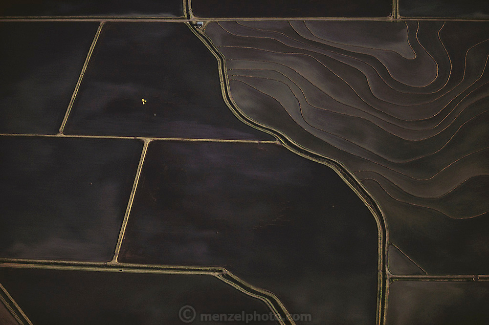 Aerial photograph of flooded rice fields in central valley California. A biplane is seeding rice by Air. Near Richvale, California.