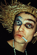 Man smoking wearing straw hat and humorous make-up, Hellfire club, London, U.K, 2000.